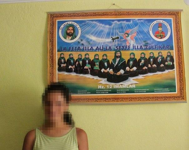 """Армянка в доме, в Дерсиме, позирует с изображением Двенадцати Имамов. Она узнала, что она армянка в 15 лет. Для незнакомцев, она алевит заза, но ее друзья и соседи в Дерсиме знают, что она армянка и христианка. Она говорит, что не боится быть известной как армянка в Дерсиме, """"но я боюсь за свою жизнь, если об этом узнают в университете"""", где она получает степень бакалавра в области экономики. / А. Хаджян"""